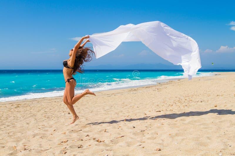 Bella ragazza con tessuto bianco sulla spiaggia. fotografia stock