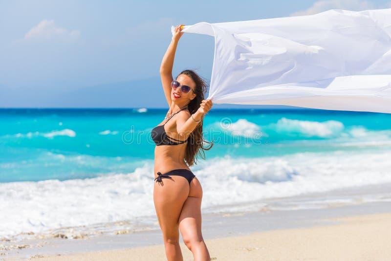 Bella ragazza con tessuto bianco sulla spiaggia. fotografia stock libera da diritti