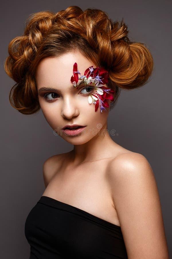 Bella ragazza con trucco creativo con gli applique floreali Il modello nello stile di romantico con i petali del fiore intorno ai immagini stock