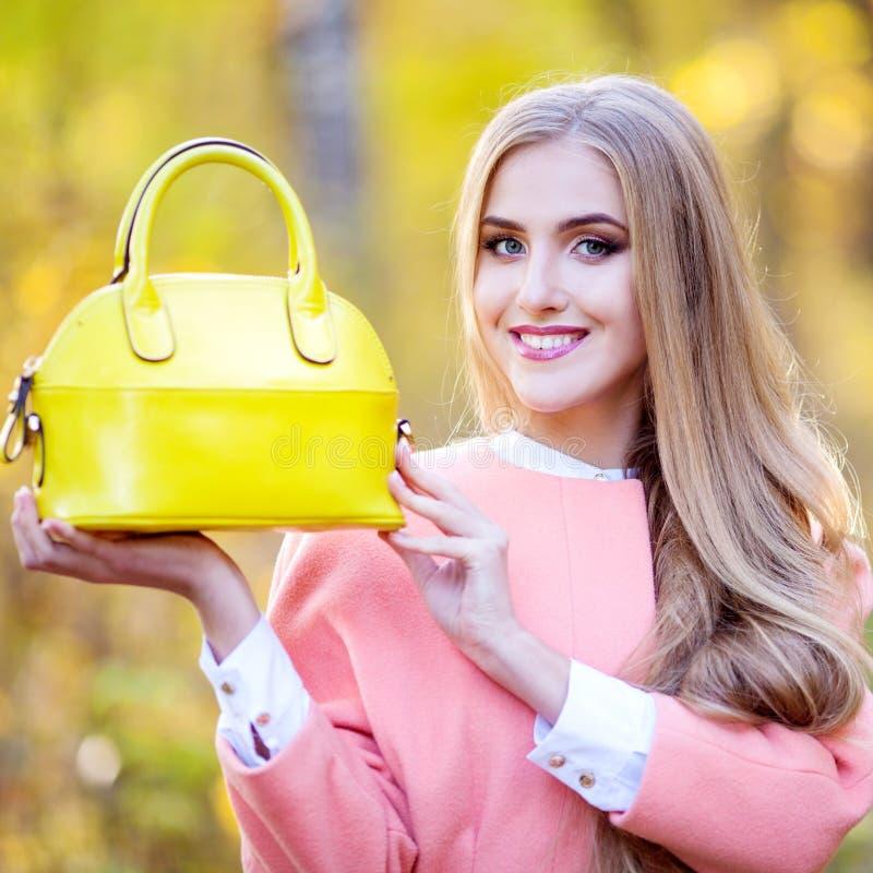 Bella ragazza con un giorno giallo di autunno della borsa di cuoio in natura fotografia stock