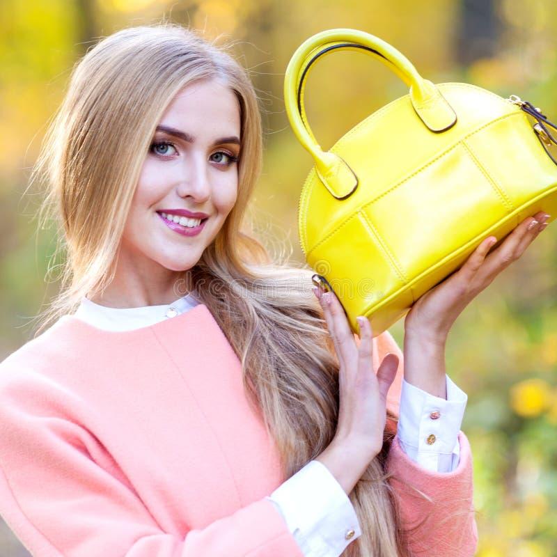 Bella ragazza con un giorno giallo di autunno della borsa di cuoio in natura immagini stock libere da diritti