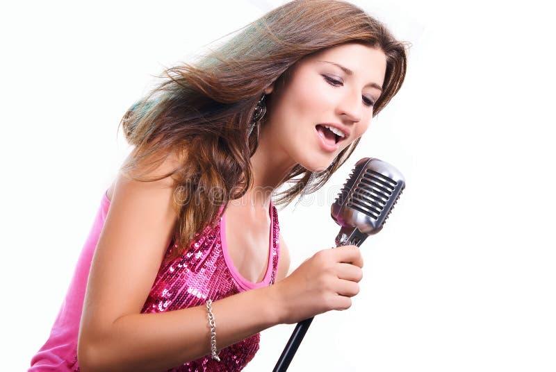 Bella ragazza con un microfono che canta una canzone fotografia stock libera da diritti