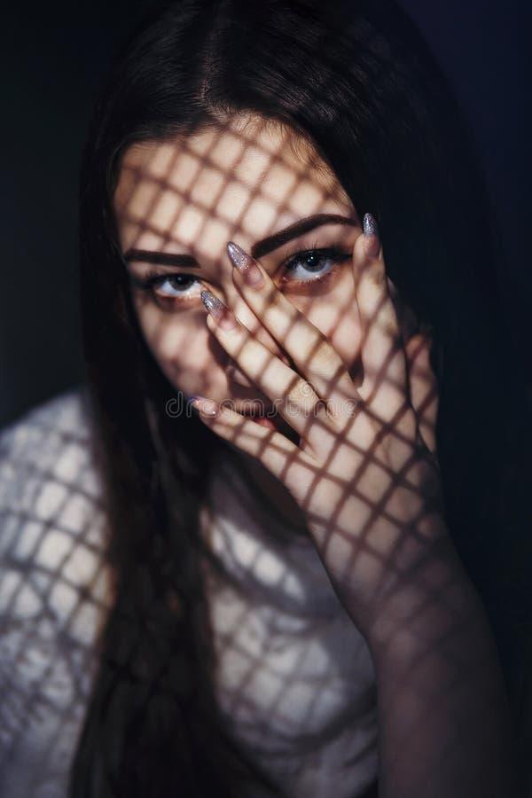 Bella ragazza con un modello leggero sul fronte sotto forma di griglia, un ritratto di una giovane donna con un segreto che copre fotografie stock