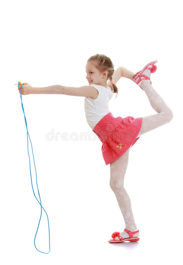 Bella ragazza con un salto della corda giallo in vostro immagine stock libera da diritti