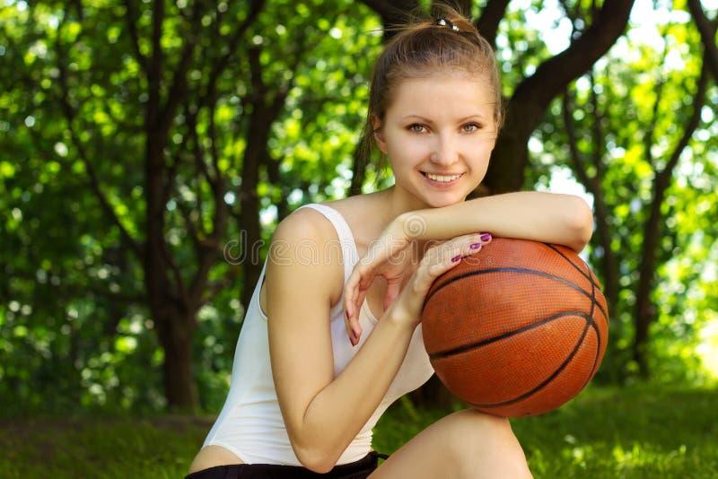 Bella ragazza con un sorriso, sedentesi con una palla di pallacanestro dentro per gli sport immagine stock