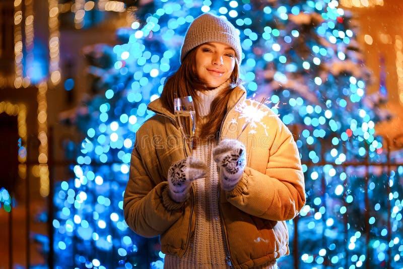 Bella ragazza con un vetro di champagne e scintillare all'aperto sui precedenti dell'albero di Natale in un inverno fotografie stock libere da diritti