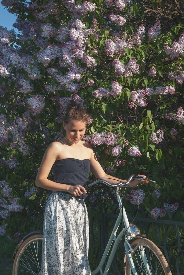 Bella ragazza con una bicicletta di estate del parco immagini stock libere da diritti