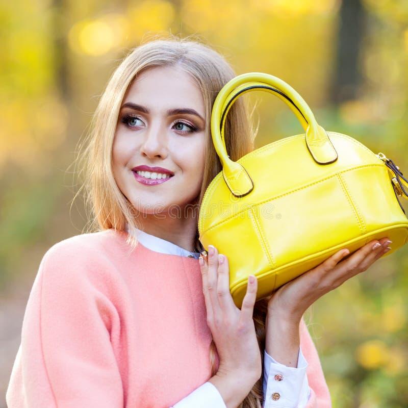 Bella ragazza con una borsa di cuoio in autunno sulla natura immagine stock libera da diritti