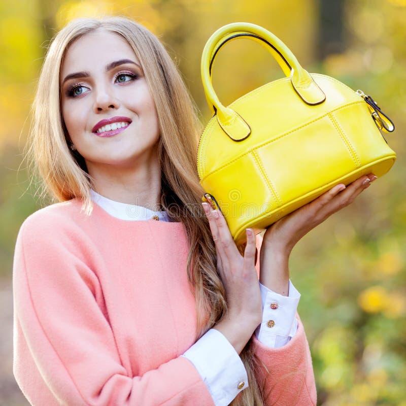 Bella ragazza con una borsa di cuoio in autunno sulla natura immagini stock