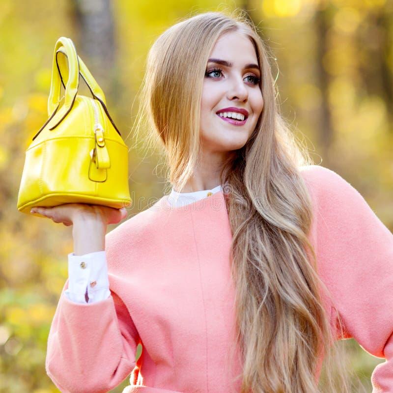 Bella ragazza con una borsa di cuoio gialla all'aperto fotografia stock libera da diritti
