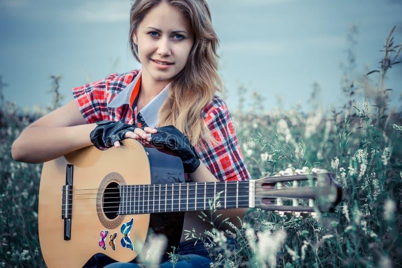 Bella ragazza con una chitarra immagini stock
