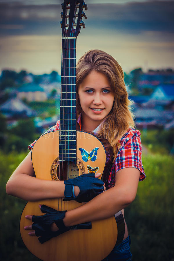 Bella ragazza con una chitarra fotografia stock