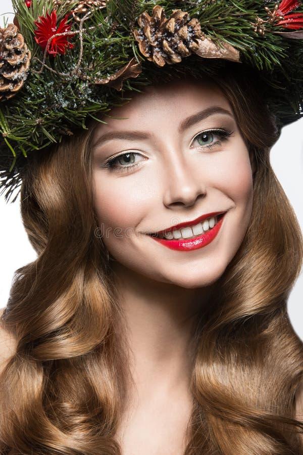 Bella ragazza con una corona dei rami e dei coni dell'abete Immagine di nuovo anno Fronte di bellezza fotografia stock