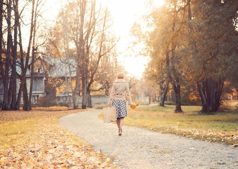 Bella ragazza con una valigia in un parco fotografie stock libere da diritti