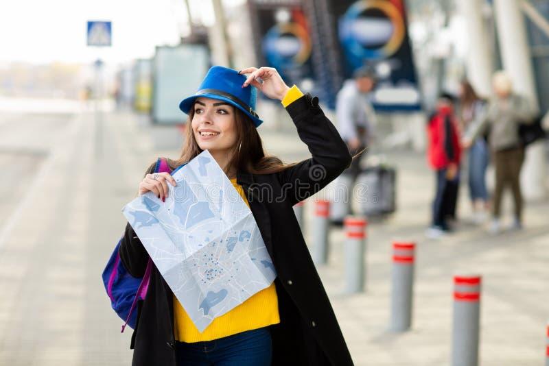 Bella ragazza con uno zaino dietro la sua spalla che tiene una mappa, nella via vicino all'aeroporto fotografia stock