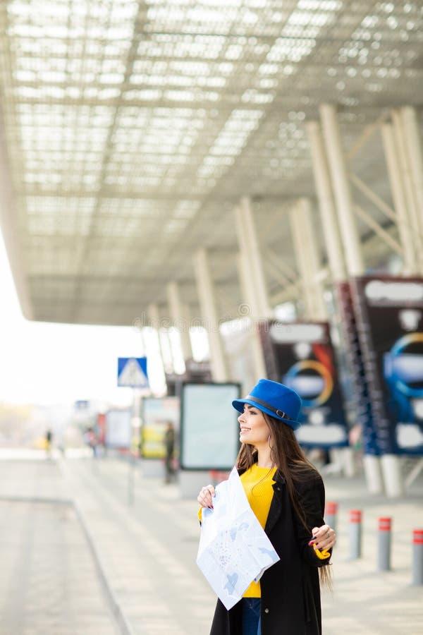 Bella ragazza con uno zaino dietro la sua spalla che tiene una mappa, nella via vicino all'aeroporto immagine stock