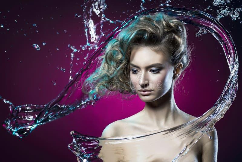 Bella ragazza coperta di spruzzata dell'acqua su un backg viola immagini stock libere da diritti