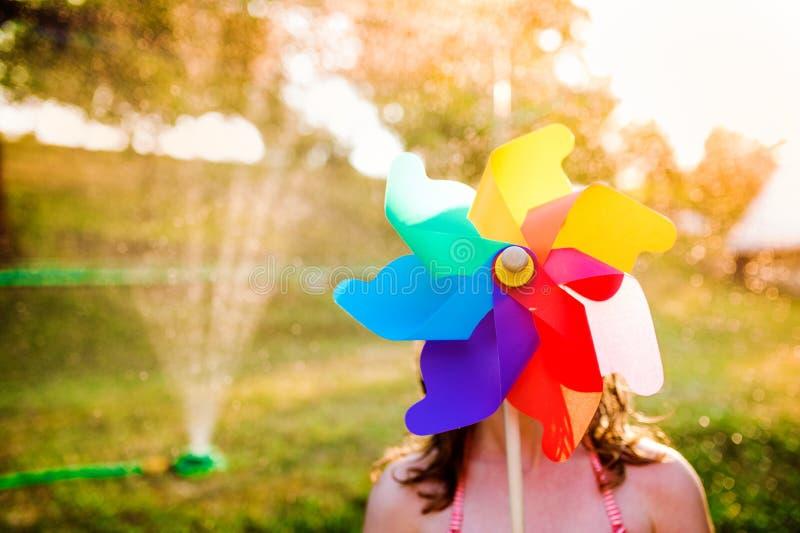 Bella ragazza in costume da bagno che si nasconde dietro la girandola, giardino di estate fotografia stock libera da diritti