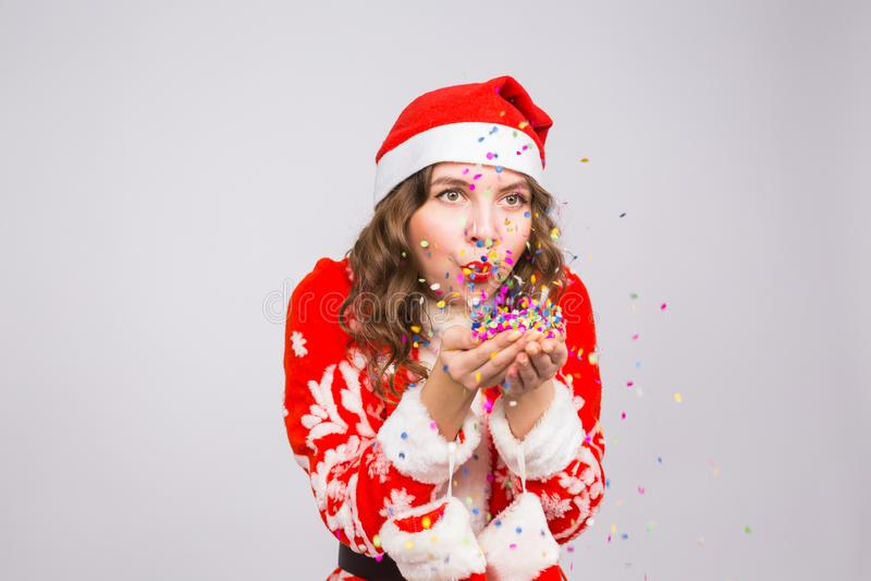 Bella ragazza in costume del ` s di Santa che accoglie favorevolmente i coriandoli di salto del nuovo anno 2019 alla macchina fot fotografie stock libere da diritti