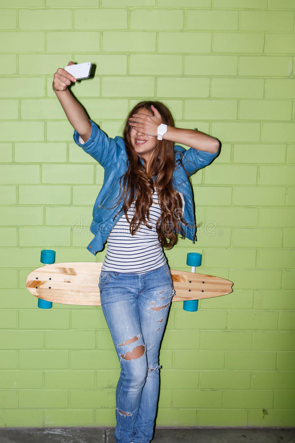 Bella ragazza dai capelli lunghi con un cellulare vicino ad un mattone verde w fotografia stock libera da diritti