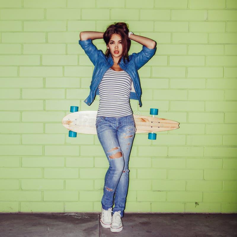Bella ragazza dai capelli lunghi con un longboard di legno vicino ad un verde fotografie stock