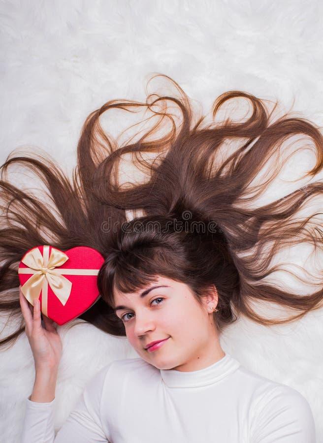 Bella ragazza dai capelli lunghi di marrone scuro con il contenitore di regalo nella forma di h immagine stock libera da diritti