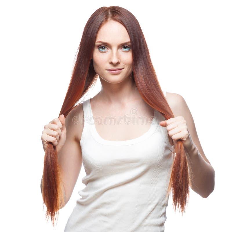 Bella ragazza dai capelli rossi che tiene i suoi capelli immagini stock
