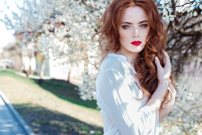 Bella ragazza dai capelli rossi sexy con le lentiggini con rossetto rosso sui suoi alberi di fioritura vicini delle labbra nella  immagini stock