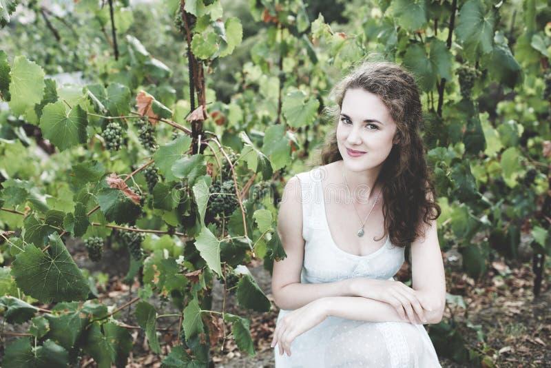 Bella ragazza dei capelli ricci in un vestito semplice blu-chiaro in una vigna fotografia stock libera da diritti