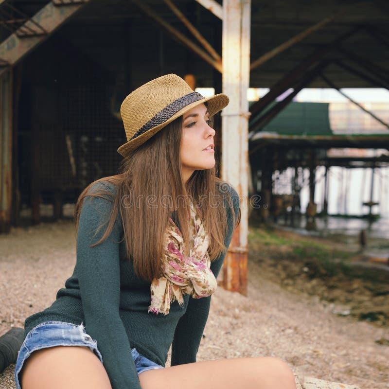 Bella ragazza dei pantaloni a vita bassa che riposa sotto il vecchio pilastro su una spiaggia del mare immagine stock