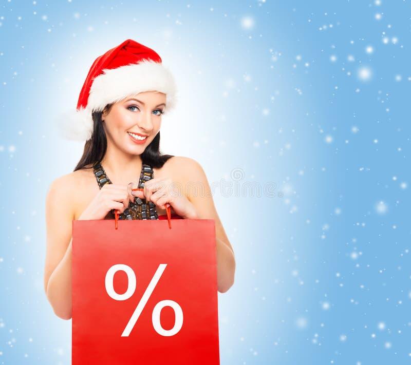 Bella ragazza del cliente di Natale su un fondo blu-chiaro fotografie stock