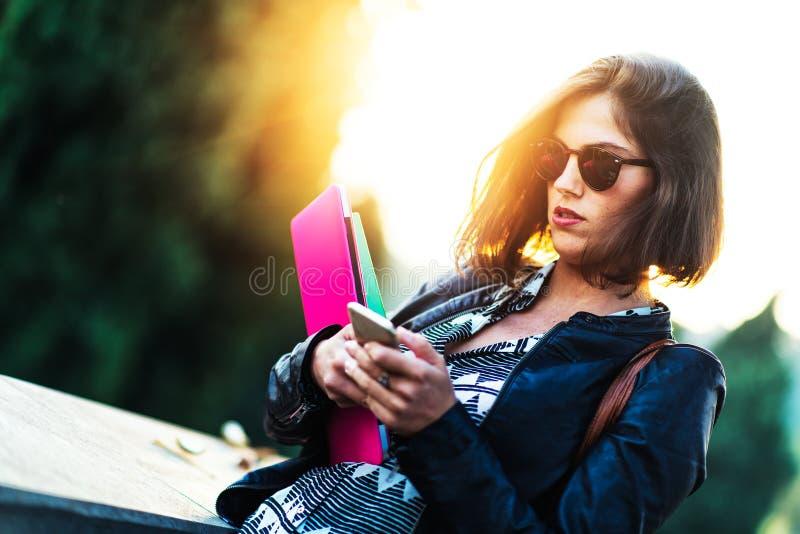 Bella ragazza del giovane studente che cammina nella città con COM dei libri fotografia stock