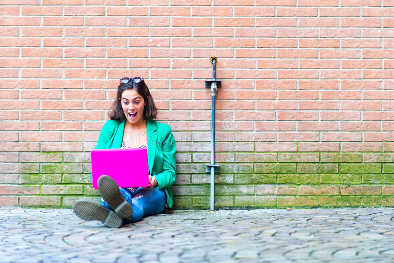 Bella ragazza del giovane studente che si siede sulla chiacchierata al suolo sul socia immagini stock