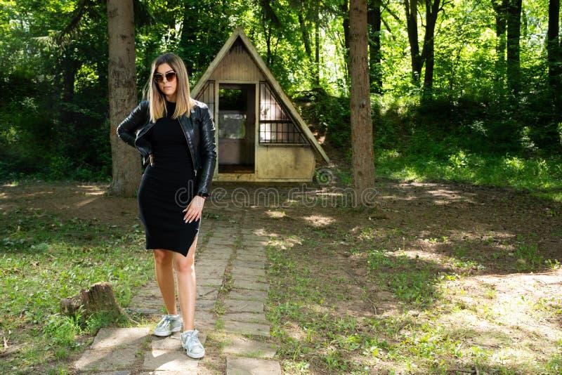 Bella ragazza del modello di moda con gli occhiali da sole, il vestito nero ed il bomber in natura fotografia stock libera da diritti