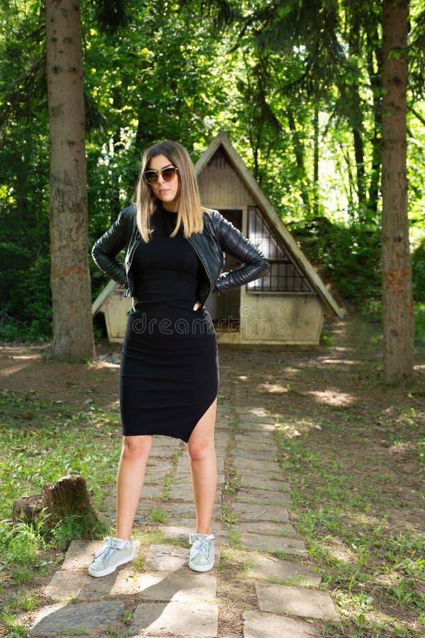 Bella ragazza del modello di moda con gli occhiali da sole, il vestito nero ed il bomber in natura con le mani sulle anche fotografia stock