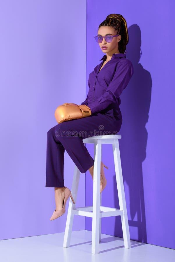 bella ragazza del mulatto in guantone da pugile che si siede sulle feci, tendenza ultravioletta di fotografia stock