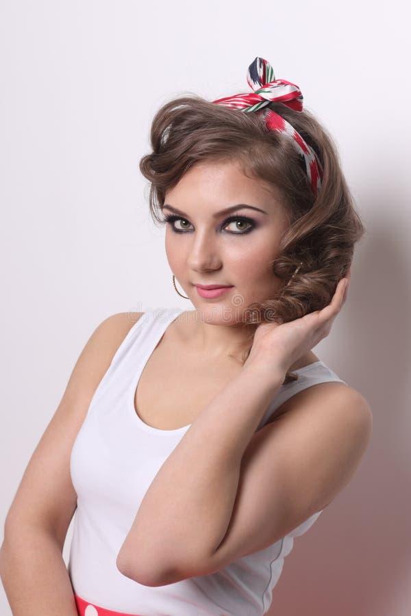 Bella ragazza del Pinup nel bianco e con capelli ricci fotografia stock