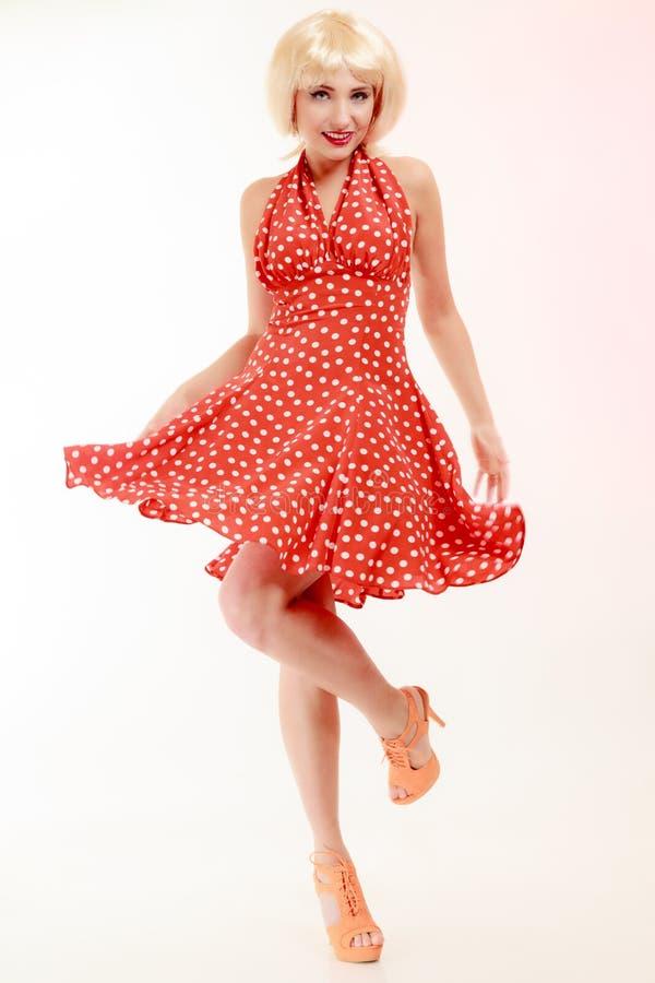 Bella ragazza del pinup in parrucca bionda e nel retro dancing rosso del vestito. Partito. immagine stock