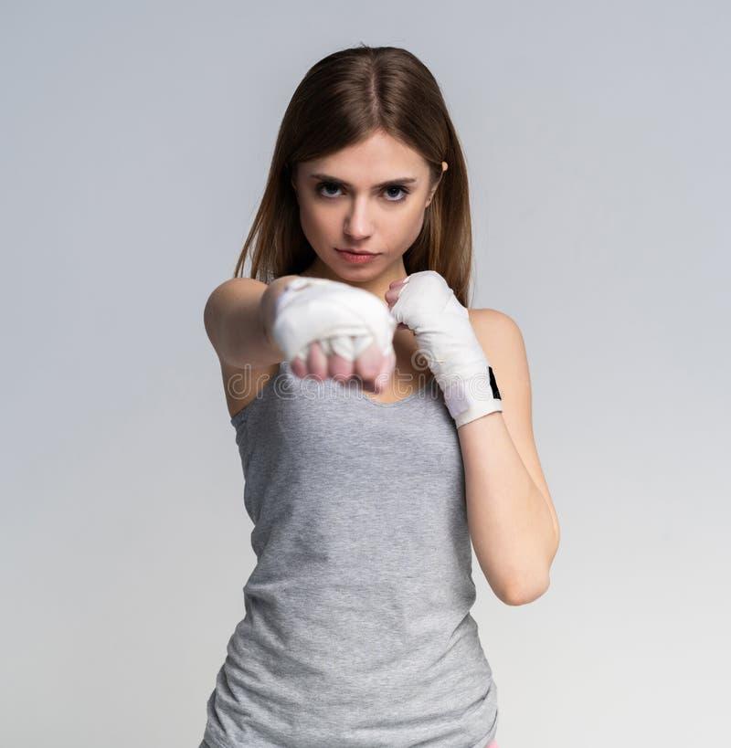 Bella ragazza del pugile che indossano abbigliamento allegro e guanti che praticano nello studio sopra fondo grigio, ente atletic immagini stock libere da diritti
