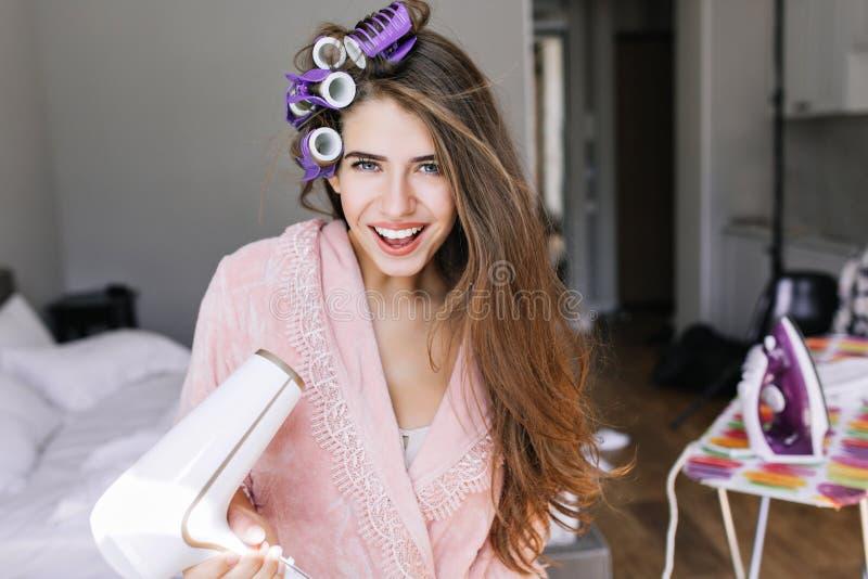 Bella ragazza del ritratto in accappatoio rosa con i curles sulla testa a casa Tiene il hairdryer, sorridente alla macchina fotog immagine stock libera da diritti