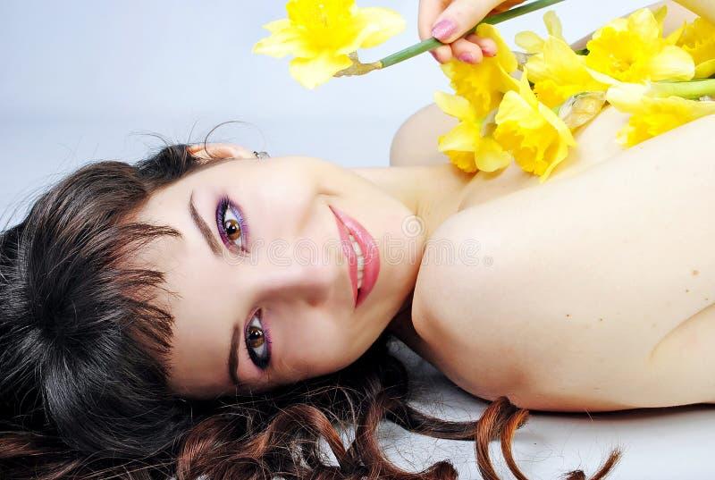 Bella ragazza del ritratto con capelli lunghi con il narciso immagine stock