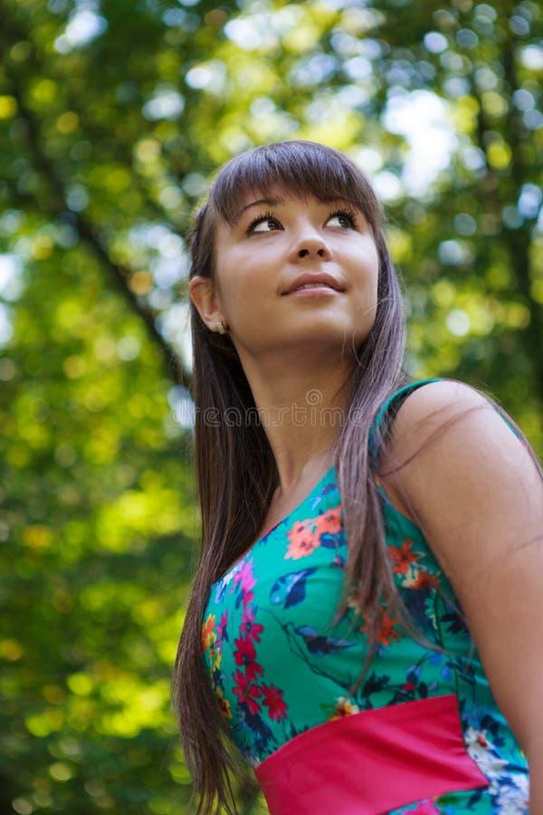 Bella ragazza del ritratto in una sosta di verde di estate immagine stock