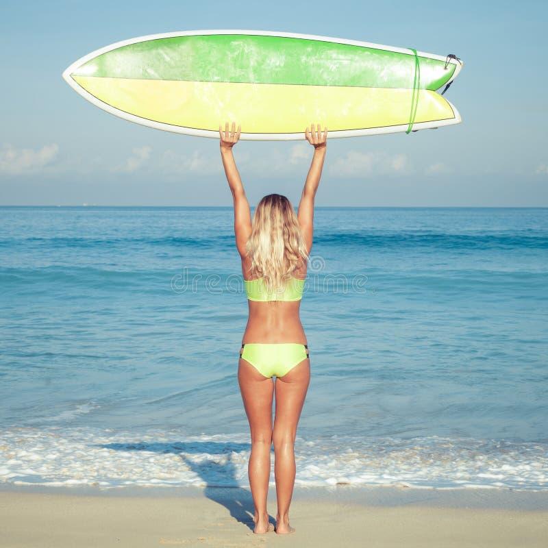 Bella ragazza del surfista sulla spiaggia fotografie stock