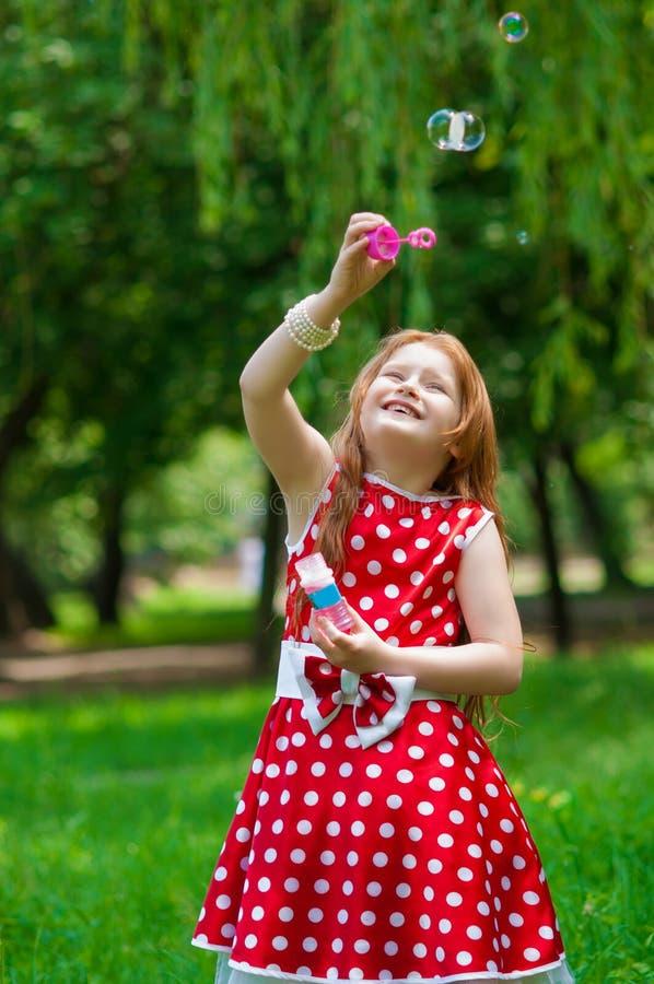Bella ragazza del vestito con le bolle di sapone fotografie stock libere da diritti