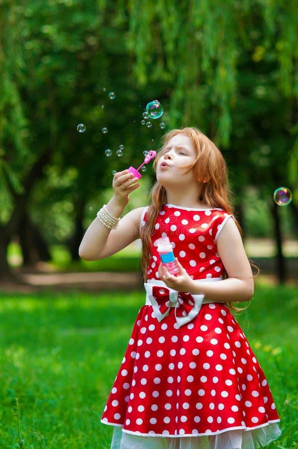 Bella ragazza del vestito con le bolle di sapone fotografie stock