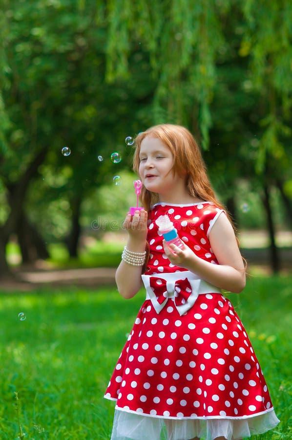 Bella ragazza del vestito con le bolle di sapone fotografia stock