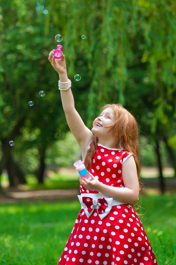 Bella ragazza del vestito con le bolle di sapone immagini stock libere da diritti