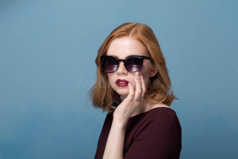 Bella ragazza della testarossa in un trucco luminoso del rossetto rosso marrone rossiccio della blusa in occhiali da sole neri su immagine stock libera da diritti