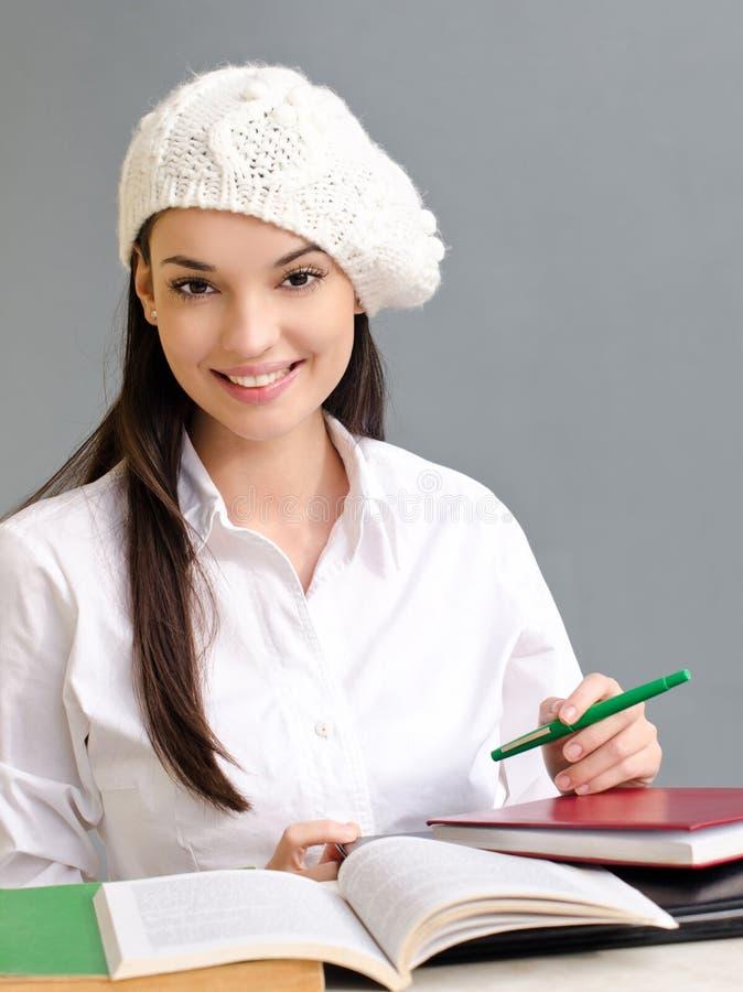 Bella ragazza dello studente che porta un berreto. fotografia stock