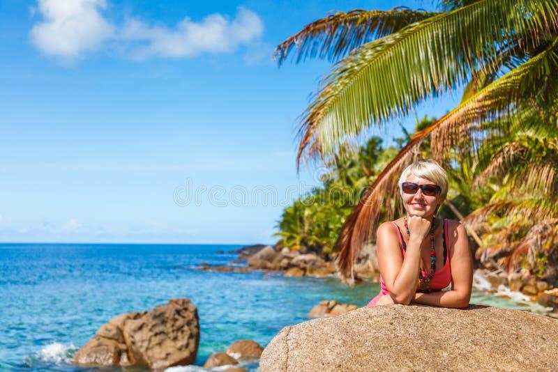 Bella ragazza dentro in vestiti luminosi che posano sotto una palma su una spiaggia tropicale immagine stock libera da diritti